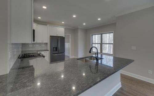 Granite Counter Tops | Hardwood Flooring | Modern Custom Farmhouse | North Georgia New Home Construction | Open Concept Kitchen And Living Area | White Kitchen Cabinetry